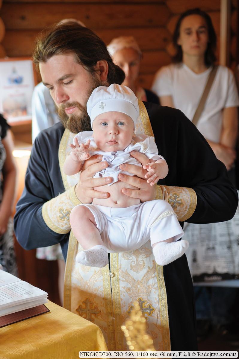 Священнослужитель часто берет ребенка на руки